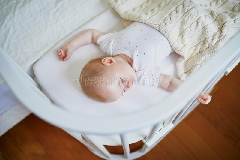 Baby sleeping in co-sleeper crib attached to parents` bed. Adorable baby girl sleeping in co-sleeper crib attached to parents` bed. Little child having a day nap royalty free stock photos