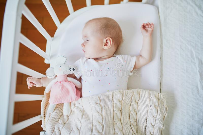Baby sleeping in co-sleeper crib attached to parents` bed. Adorable baby girl sleeping in co-sleeper crib attached to parents` bed with stuffed toy. Little child stock photography