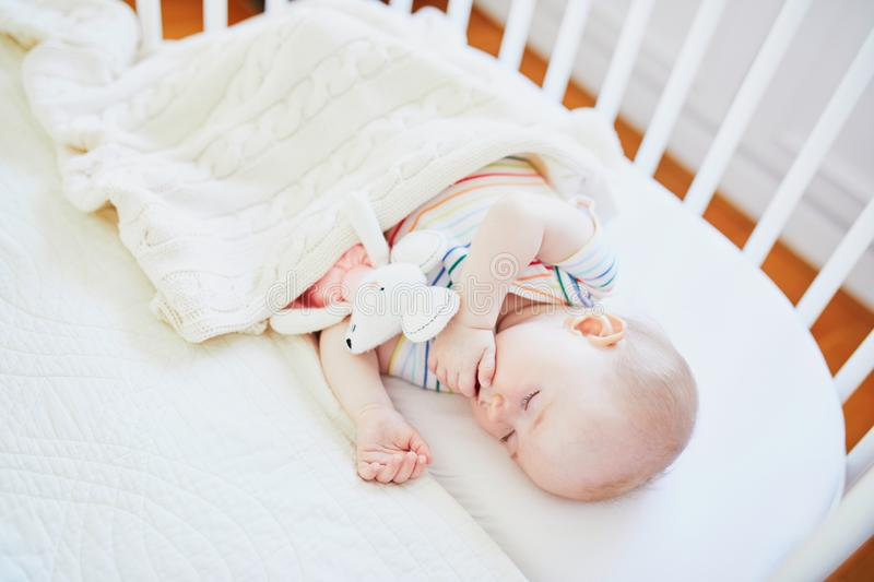 Baby sleeping in co-sleeper crib attached to parents` bed. Adorable baby girl sleeping in co-sleeper crib attached to parents` bed with stuffed toy. Little child stock photo