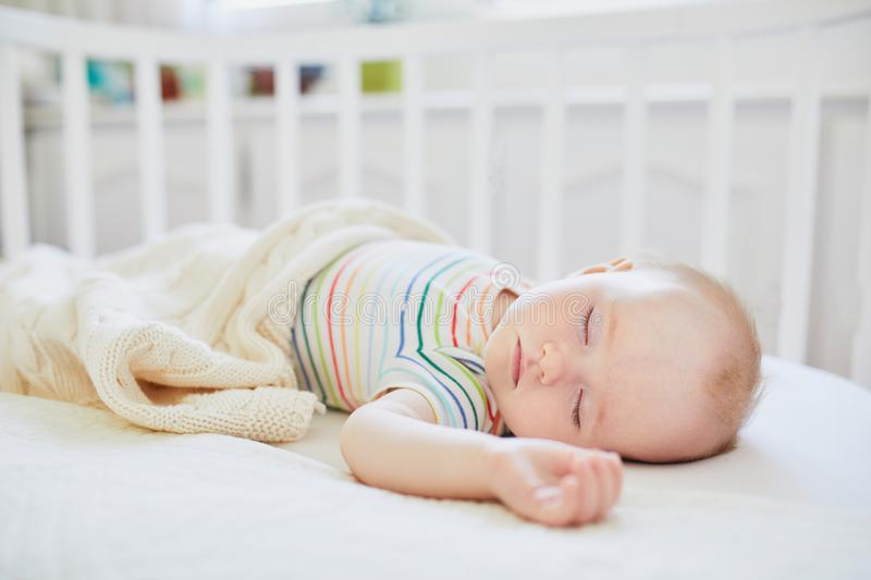 Baby sleeping in co-sleeper crib attached to parents` bed. Adorable baby girl sleeping in co-sleeper crib attached to parents` bed. Little child having a day nap stock images