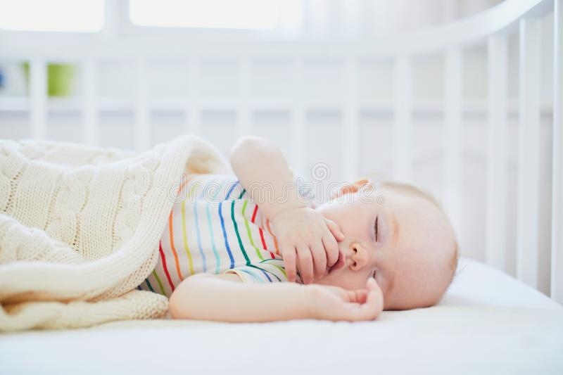 Baby sleeping in co-sleeper crib attached to parents` bed. Adorable baby girl sleeping in co-sleeper crib attached to parents` bed. Little child having a day nap royalty free stock photo
