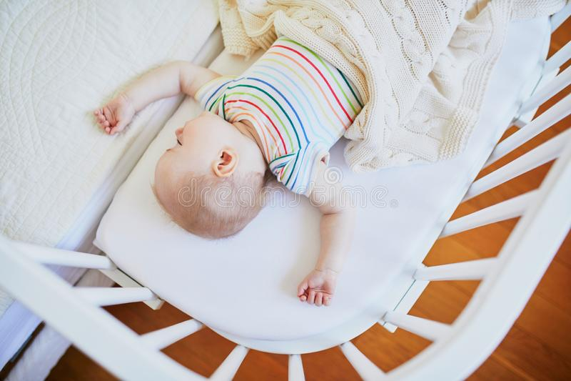 Baby sleeping in co-sleeper crib attached to parents` bed. Adorable baby girl sleeping in co-sleeper crib attached to parents` bed. Little child having a day nap stock photo