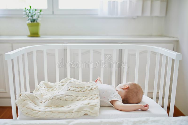 Baby sleeping in co-sleeper crib attached to parents` bed royalty free stock photo