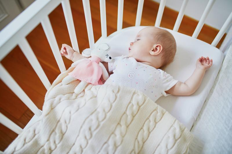 Baby sleeping in co-sleeper crib attached to parents` bed. Adorable baby girl sleeping in co-sleeper crib attached to parents` bed with stuffed toy. Little child stock photos