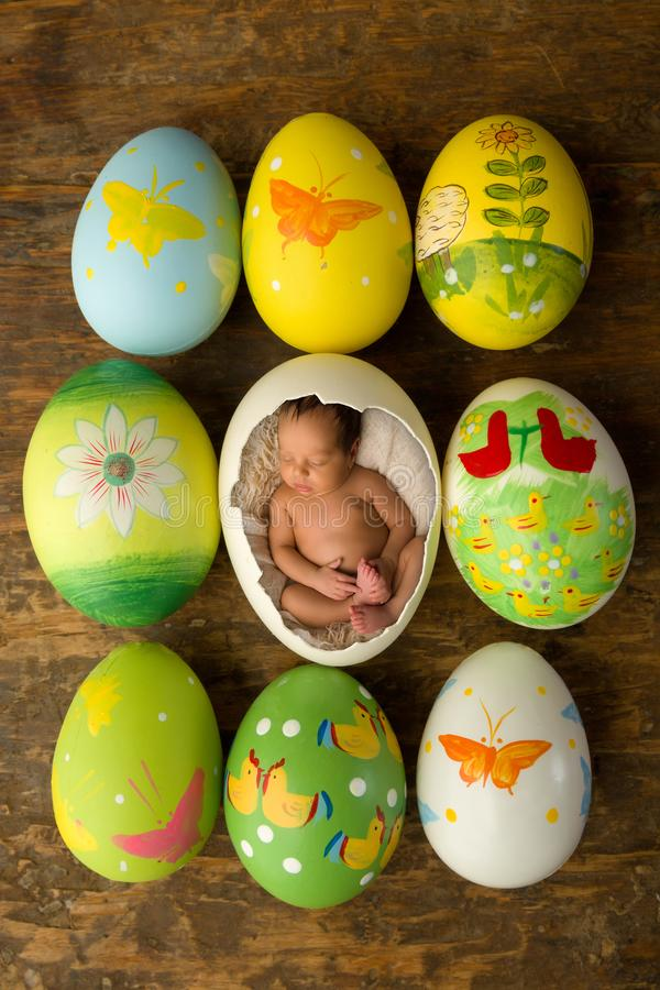 Newborn baby in Easter eggs stock photos