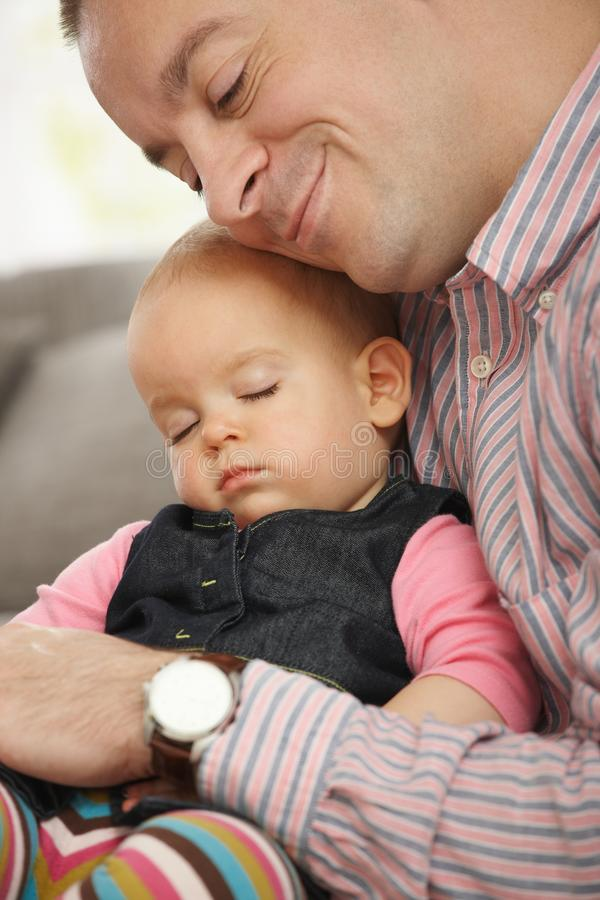 Baby sleeping in father's arm. Cute little baby sleeping held in father's arm at home royalty free stock photos