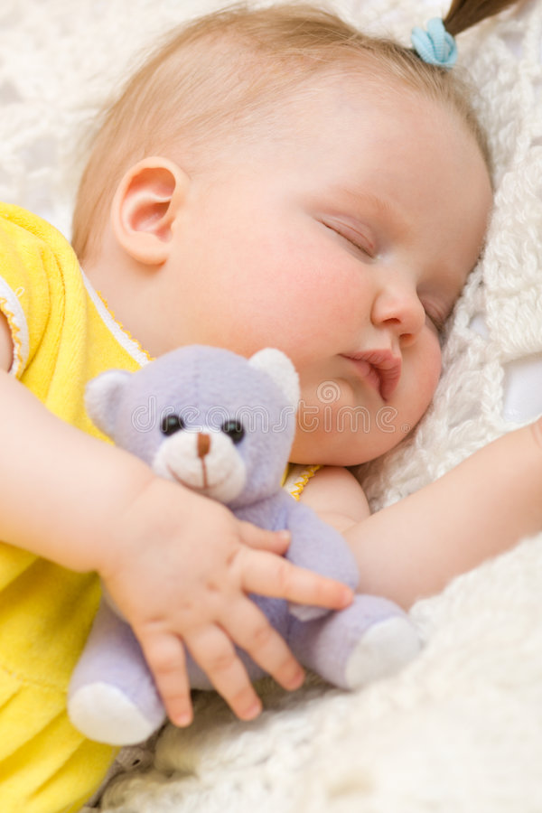 Baby sleeping with her bear toy stock image