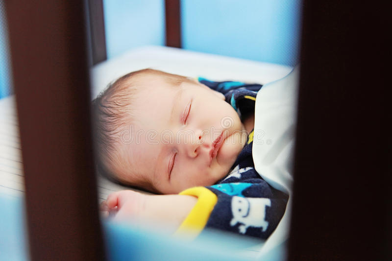 Baby sleeping. Newborn baby sleeping in crib with blanket stock photography