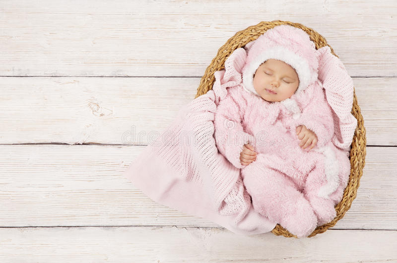 Baby Sleeping, Newborn Kid Sleep in Pink Clothing, New Born. Child Asleep in Basket over Wood Background stock images