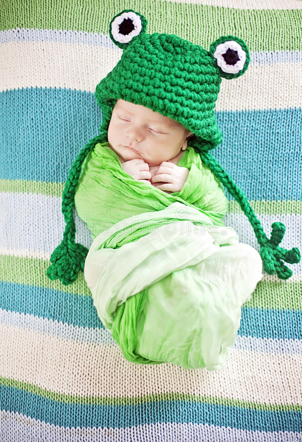Baby sleeping. Newborn baby sleeping while wrapped in green blanket wearing frog hat royalty free stock images