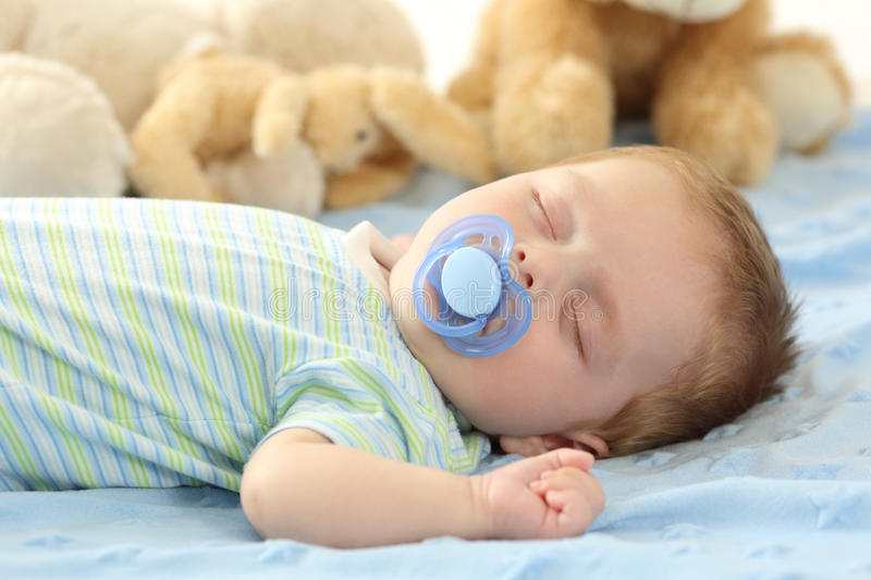 Baby sleeping with a pacifier. Cute baby sleeping with a pacifier on a bed stock images