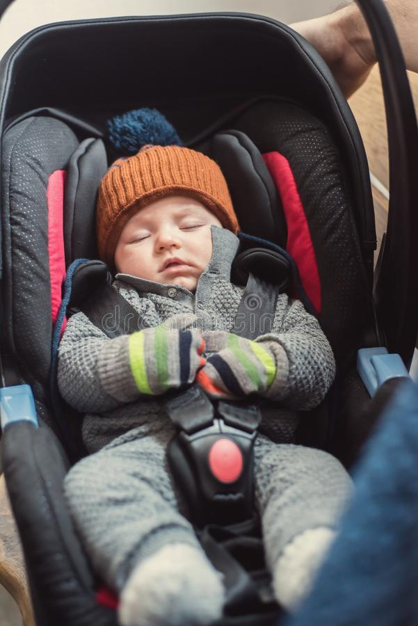 Baby sleeping in safety car seat. A three months old baby sleeping in a safety car seat or carrier. Safety concept,indoors shot stock photo