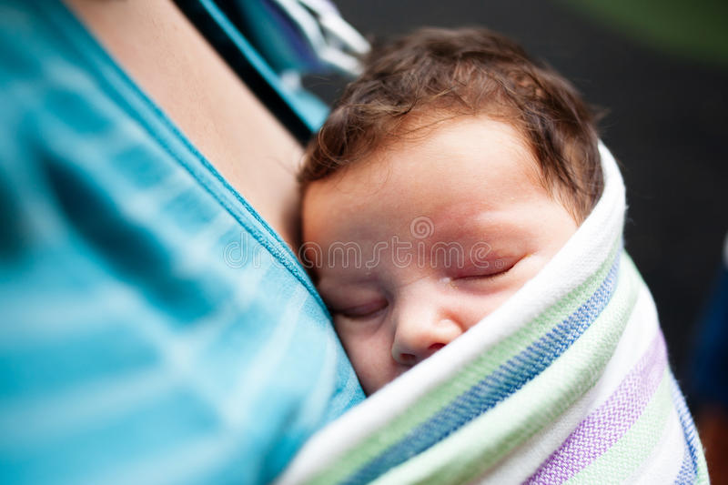 Baby sleeping in sling. Baby sleeping against mothers chest in sling stock images