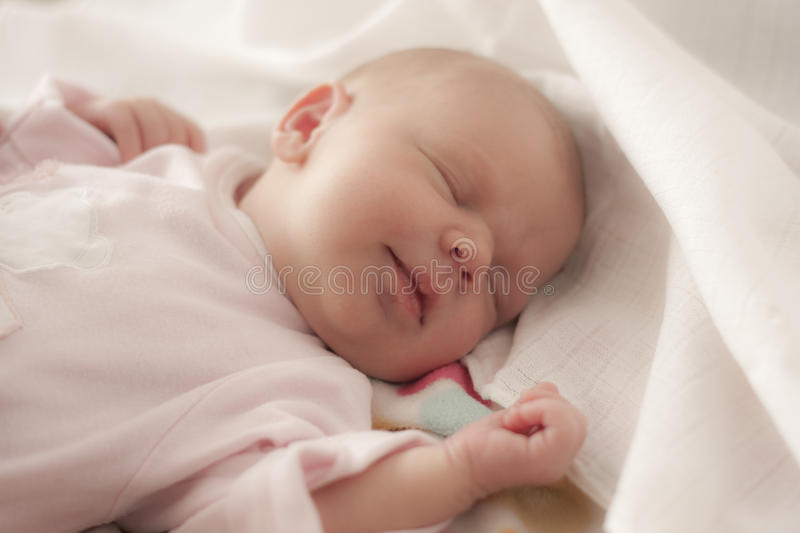 Baby sleeping with a smile. Newborn baby sleeping with a light smile stock photos