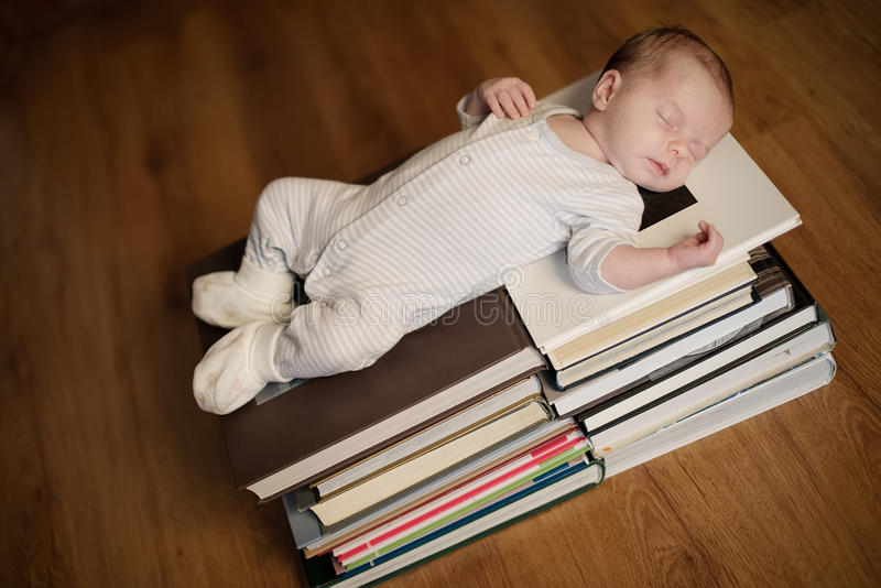 Baby sleeping on stack of books. Cute baby sleeping on stack of books stock image