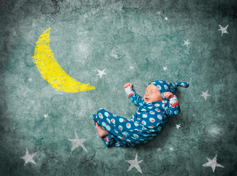 Baby sleeping with the stars. On a blue background royalty free stock photo