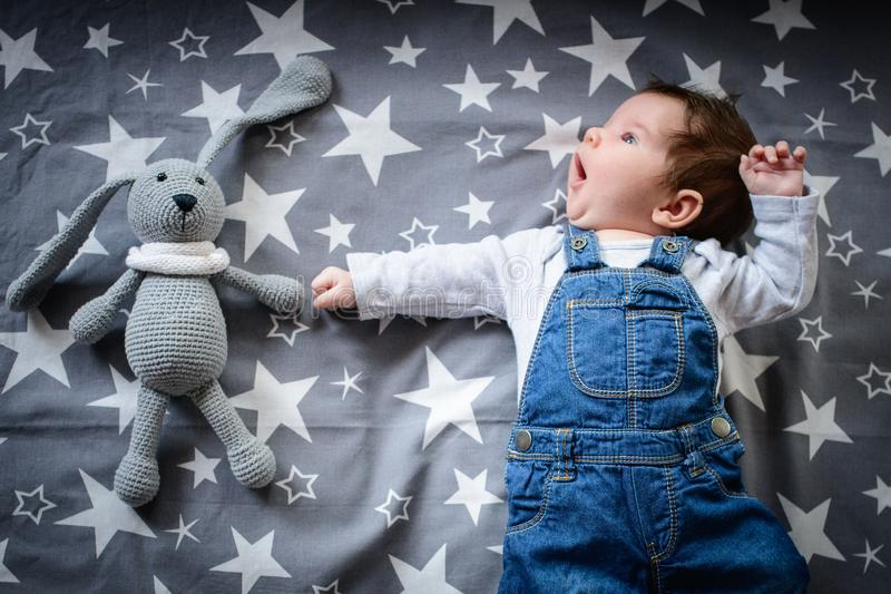 The baby is sleeping with a toy. a small child sleeps by the window, dreaming of a starry sky before going to bed. sleep concept. stock images