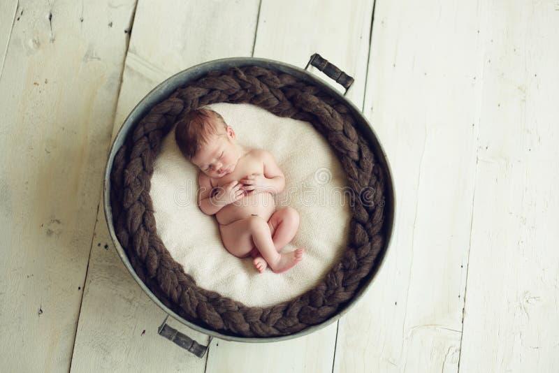 Baby sleeping in a tub. Newborn baby boy in a wash tub royalty free stock photos