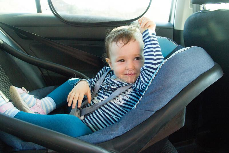 Baby smile in a safety car seat. Safety and security. one year old child girl in blue wear sit on auto cradle. Rules for the Safe. Transport of Children stock images