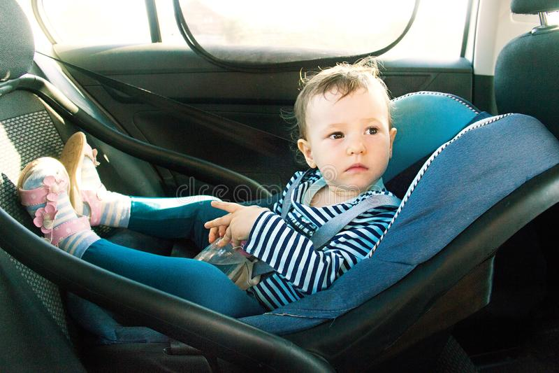 Baby smile in a safety car seat. security. one year old child girl in blue wear sit on auto cradle. Rules for the Safe Transport o stock photo