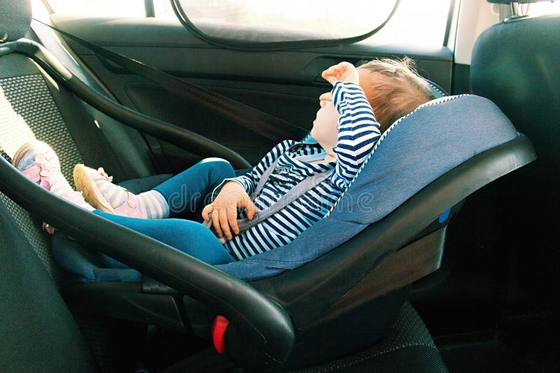 Baby smile in a safety car seat. security. one year old child girl in blue wear sit on auto cradle. Rules for the Safe Transport o royalty free stock photography