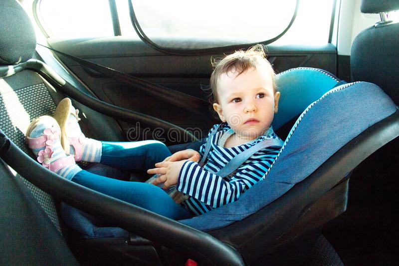 Baby smile in a safety car seat. security. one year old child girl in blue wear sit on auto cradle. Rules for the Safe Transport o royalty free stock images
