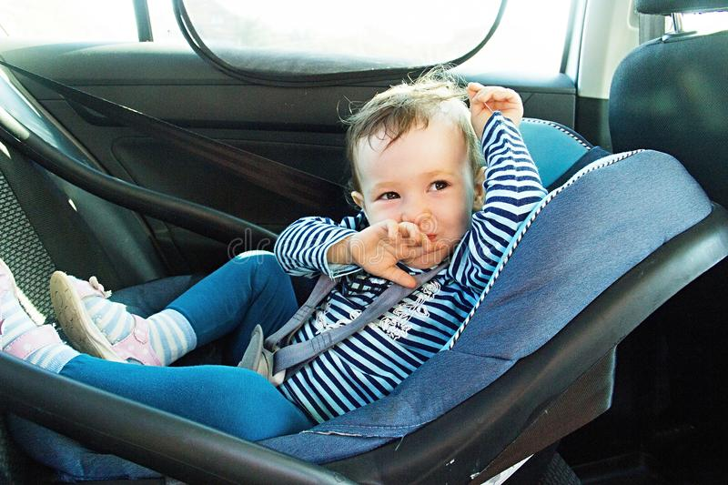 Baby smile in a safety car seat. security. one year old child girl in blue wear sit on auto cradle. Rules for the Safe Transport o. F Children. Holders royalty free stock photography