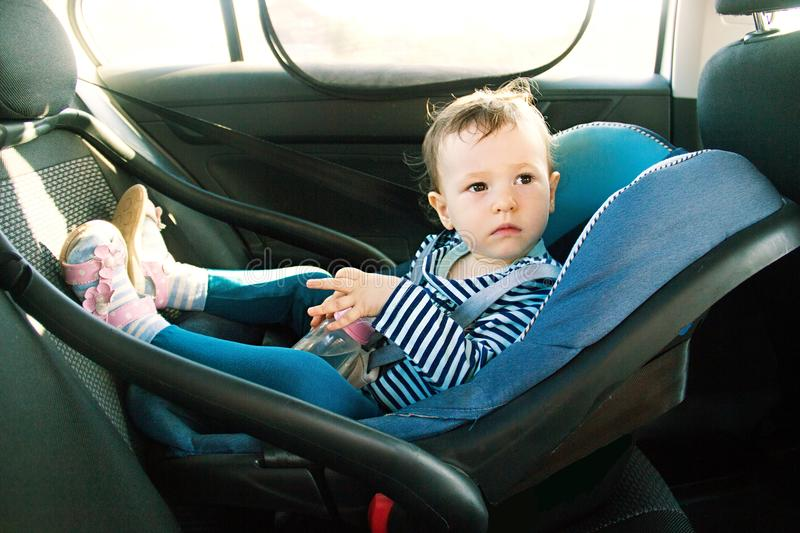 Baby smile in a safety car seat. security. one year old child girl in blue wear sit on auto cradle. Rules for the Safe Transport o. F Children. Holders stock image