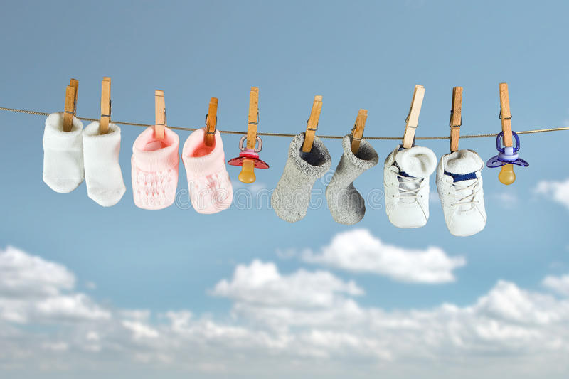 Baby socks. And shoes hanging on a clothesline in the sky stock images