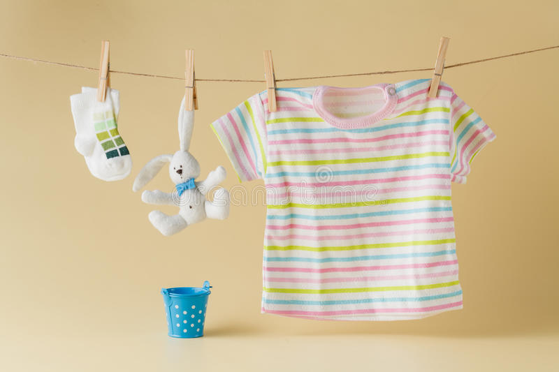 Baby socks and clothes hanging on the clothesline. Background with baby goods with copy space stock image