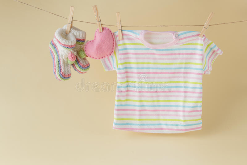 Baby socks and clothes hanging on the clothesline. Background with baby goods with copy space stock photo
