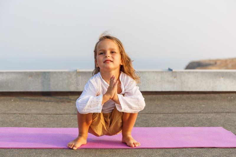 Baby som gör yoga på taket arkivfoto