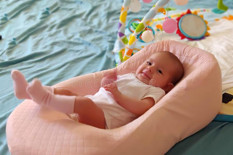 Baby som ligger i en special ortopedisk madrass, på en säng och ett leende fotografering för bildbyråer