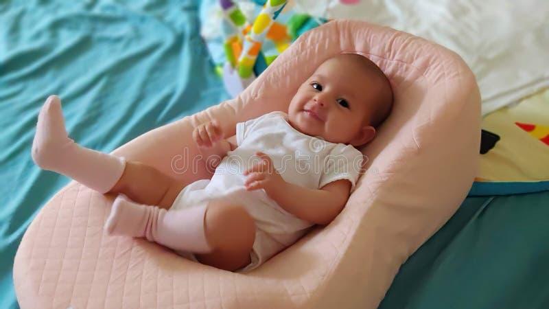 Baby som ligger i en special ortopedisk madrass, på en säng och ett leende arkivfoton