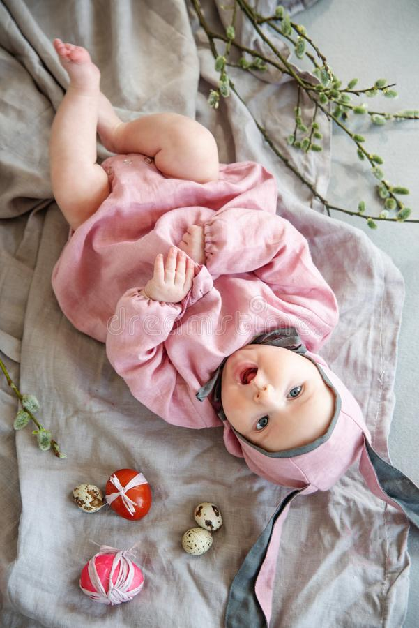 Baby som ligger på linnefilten och bär en hatt i form av en påskkanin med äggpilfilialer och påskpajen royaltyfri foto