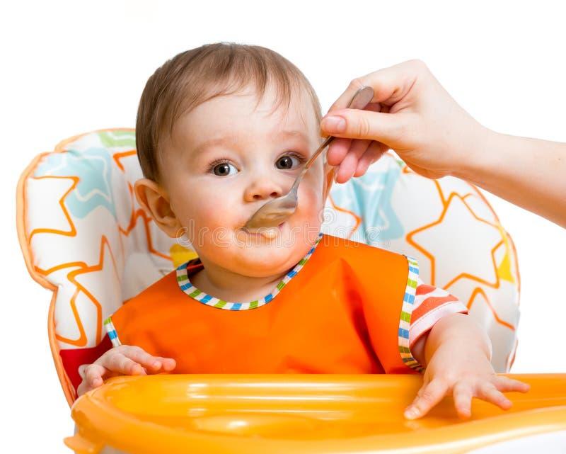 Baby som matar med en sked royaltyfria foton
