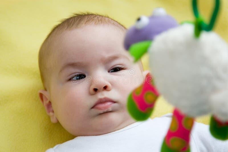 Baby som ser upp på en mobil toy royaltyfri foto