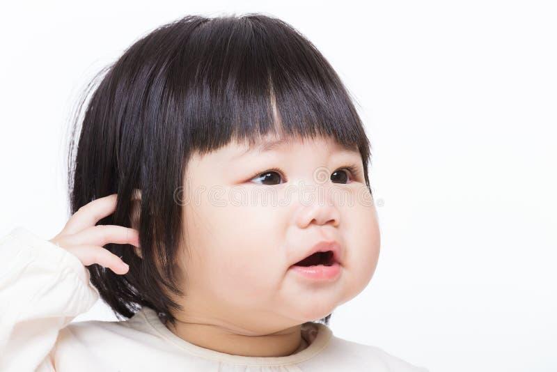 Baby som skrapar huvudet royaltyfria bilder