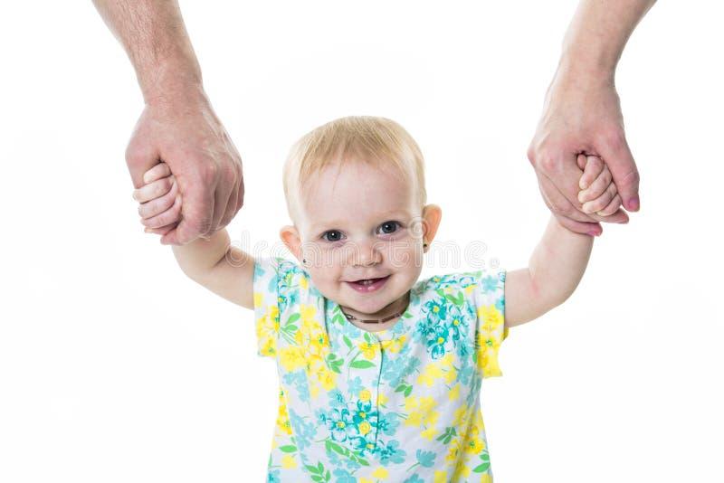 Baby som tar första steg med moderfaderhjälp på vit bakgrund royaltyfria bilder