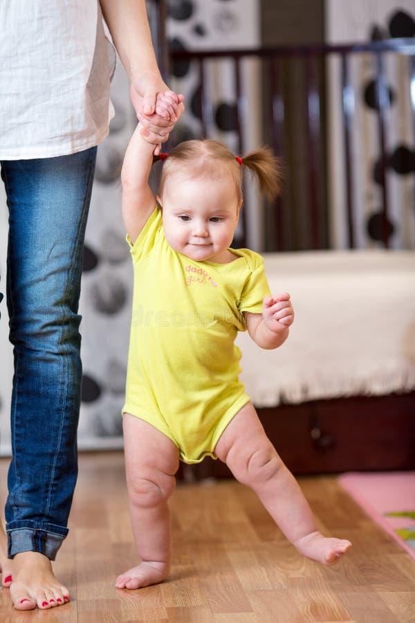 Baby som tar första steg med moderhjälp royaltyfri fotografi
