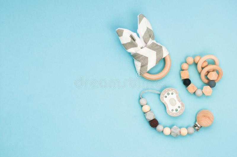 Baby soother and wooden toys on light blue background with copy space stock images