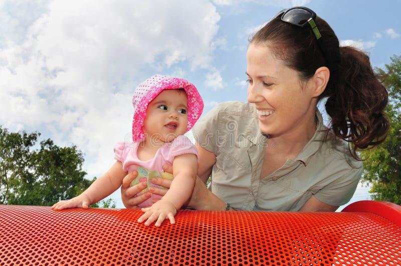 Baby-Spiele mit Mama im Spielplatz lizenzfreies stockbild