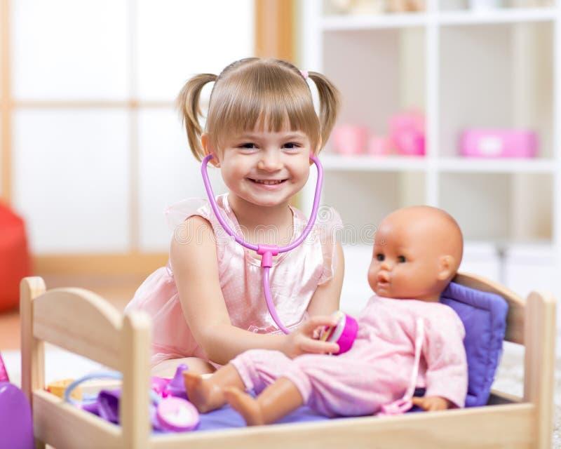 Baby spielt in Doktor mit Spielzeugpuppe und -stethoskop lizenzfreie stockfotos