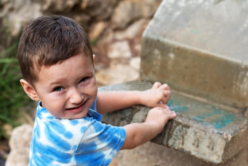 Baby in spray of water from the cooler in the park royalty free stock image