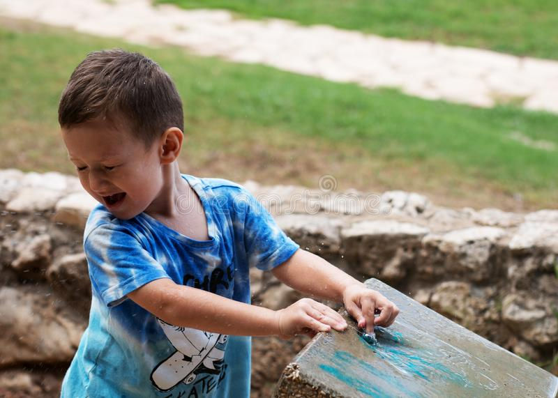 Baby in spray of water from the cooler in the park stock photography