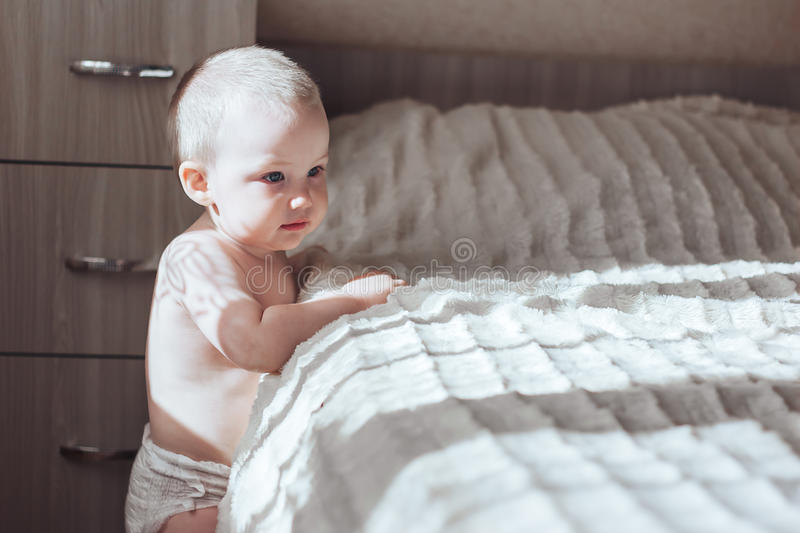 Baby stand near bed royalty free stock image