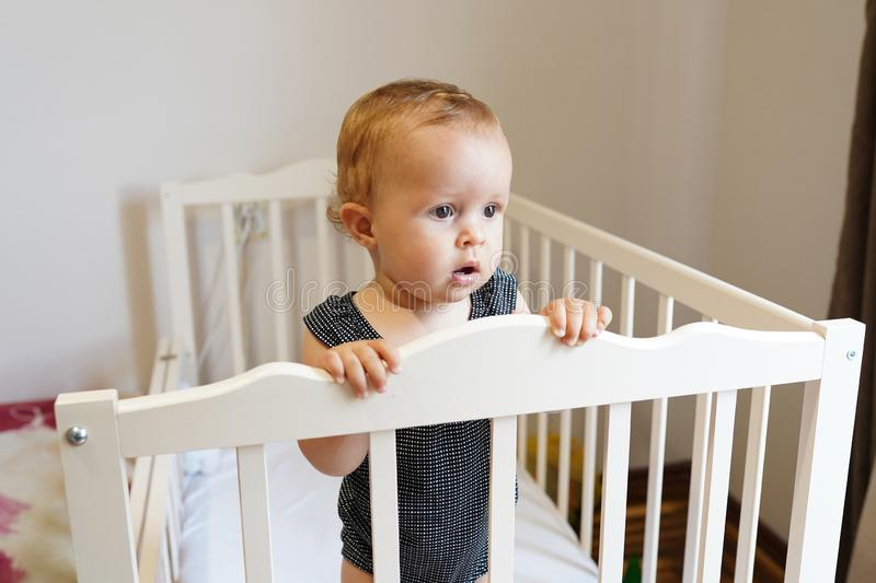 Baby standing in crib. cute Baby girl , childhood.  royalty free stock image