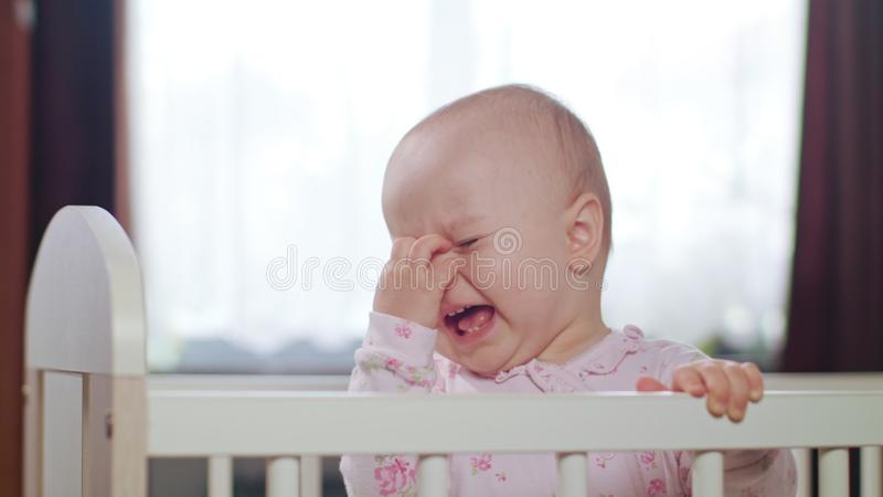 Baby Standing in a Crib at Home. Crying. Baby`s standing in a white crib at home and crying. Medium shot royalty free stock photography