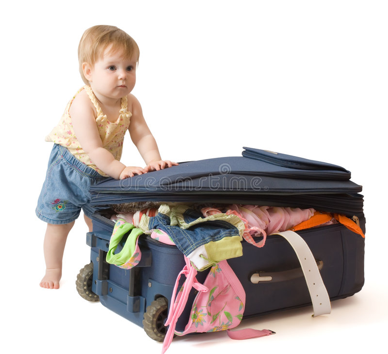 Baby standing near suitcase. Baby girl standing near the suitcase, trying to pack it, isolated, with clipping path royalty free stock photos