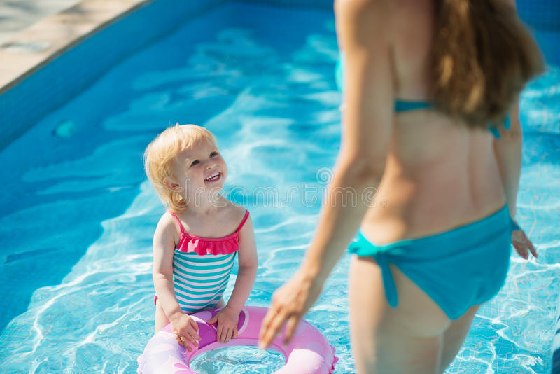 Baby standing in pool and looking on mother. Baby standing in pool with inflatable ring and looking on mother royalty free stock photo